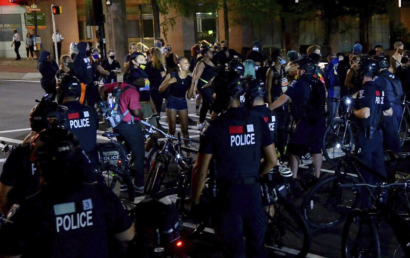 Protesters confront Charlotte Mecklenburg police bicycle officers in uptown Charlotte, N.C., on Friday night.