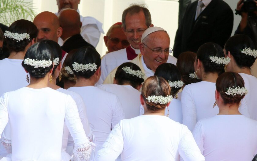Pope Francis greets a group of dancers after their presentation during Mass at Caacupe, Paraguay, on Saturday.