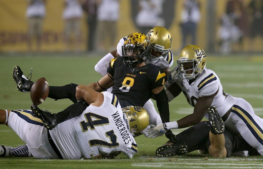 Arizona State running back D.J. Foster fumbles when brought down by UCLA defenders in the first quarter.