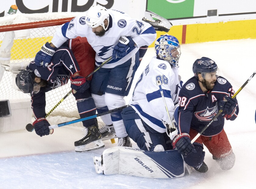 Columbus Blue Jackets left wing Nick Foligno, left, is dumped into the net by Tampa Bay Lightning defenceman Zach Bogosian (24) as Lightning goaltender Andrei Vasilevskiy (88) deals with Blue Jackets center Boone Jenner (38) during the first period of NHL Eastern Conference Stanley Cup first round playoff hockey action in Toronto, Monday, Aug. 17, 2020. (Frank Gunn/The Canadian Press via AP)