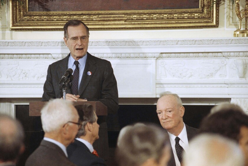 In this 1990 file photo, U.S. President George H. W. Bush, standing, addresses a White House luncheon commemorating former President Dwight. D. Eisenhower's 100th birthday. At right is John S.D. Eisenhower, the former president's son. John S.D. Eisenhower, the son of a five-star general...