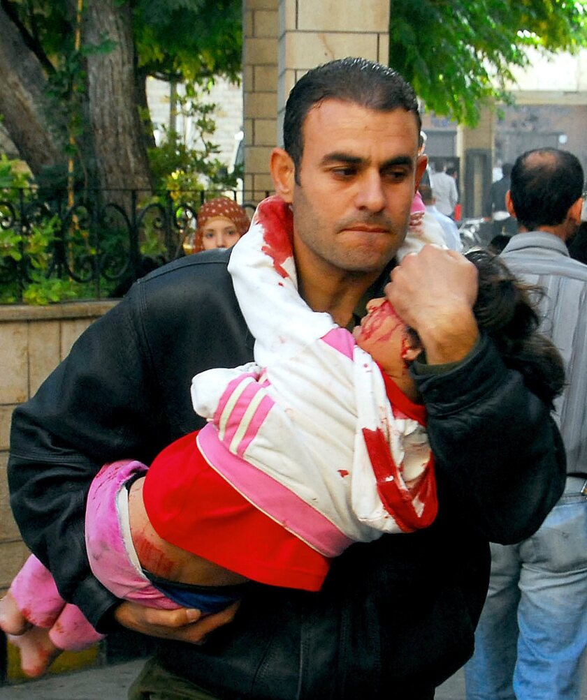 A handout photo made available by the official Syrian Arab News Agency shows a man carrying a wounded child after a car bomb Wednesday in Hijaz Square in Damascus.