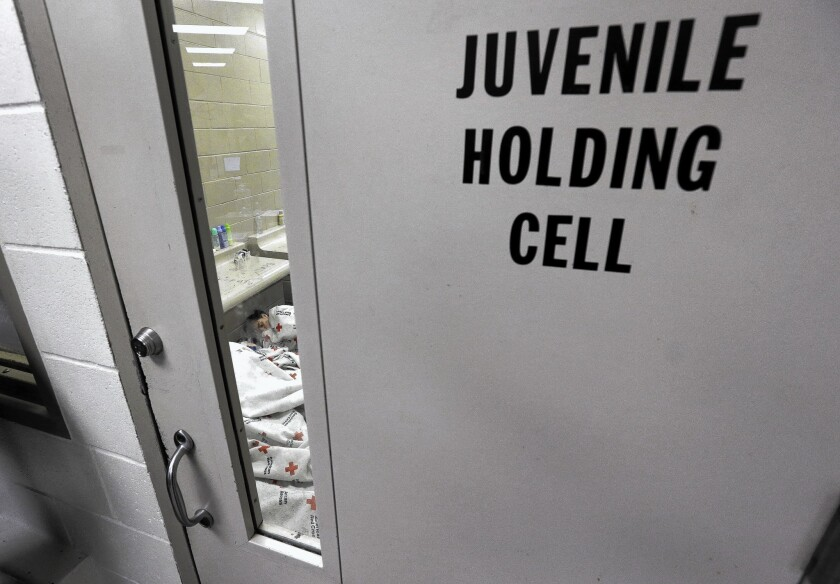 A detainee sleeps inside a holding cell at a U.S. Customs and Border Protection processing center in Brownsville, Texas.