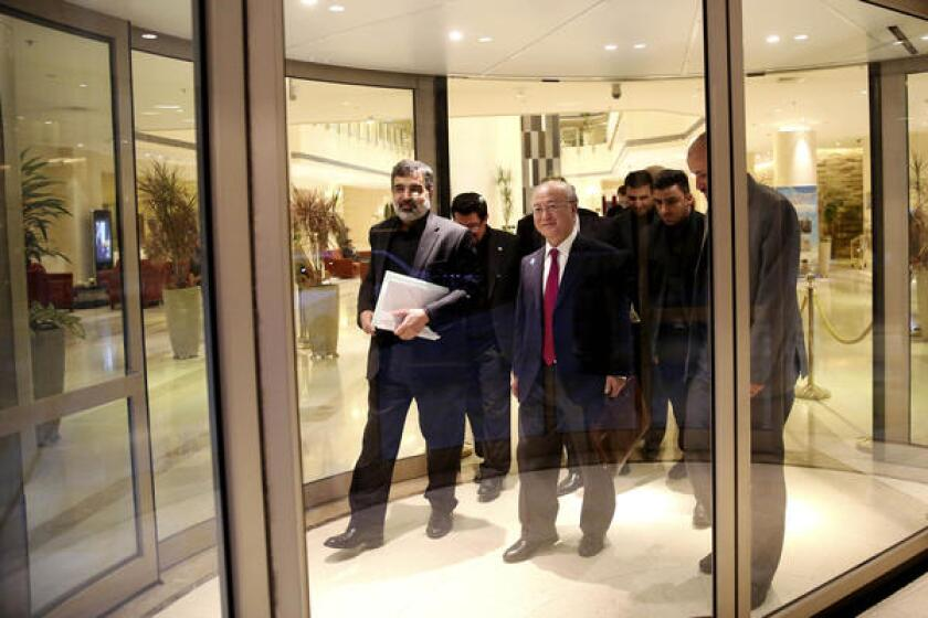 International Atomic Energy Agency Director-General Yukiya Amano, center, leaves the Azadi Hotel in Tehran after briefing reporters on the progress of nuclear negotiations with Iranian officials. Iran and the U.N. nuclear watchdog agency have reached a road map deal for cooperation that expands the monitoring of the country's nuclear sites.