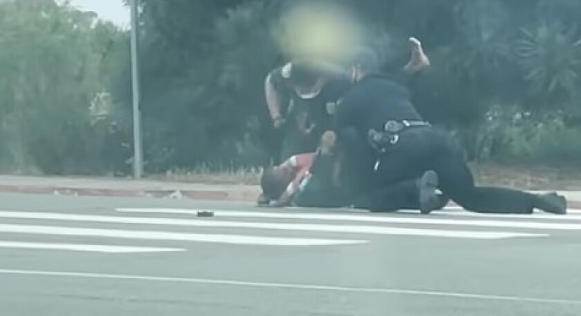 An image from a video shot by Nicole Bansal shows police officers tackling and punching Jesse Evans in La Jolla on May 12.