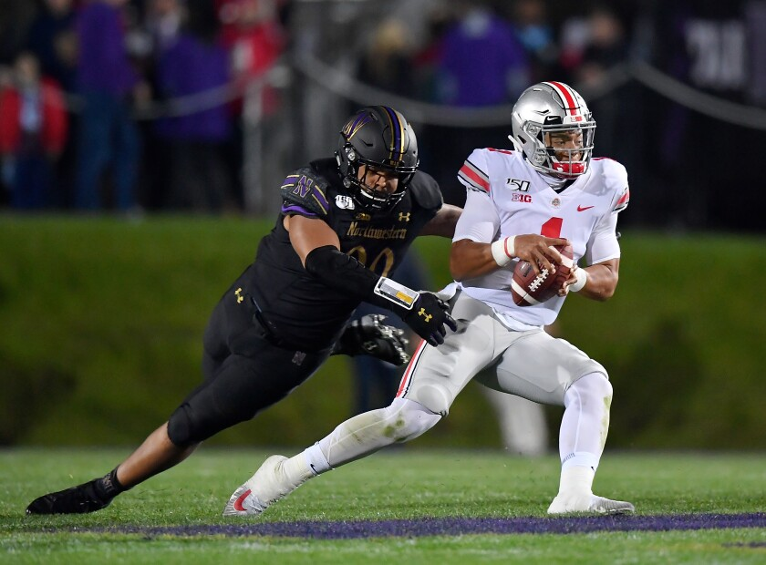 Ohio State's Justin Fields (1) scrambles in the second quarter to avoid a sack from Northwestern's Earnest Brown IV (99) on Friday in Evanston, Ill.
