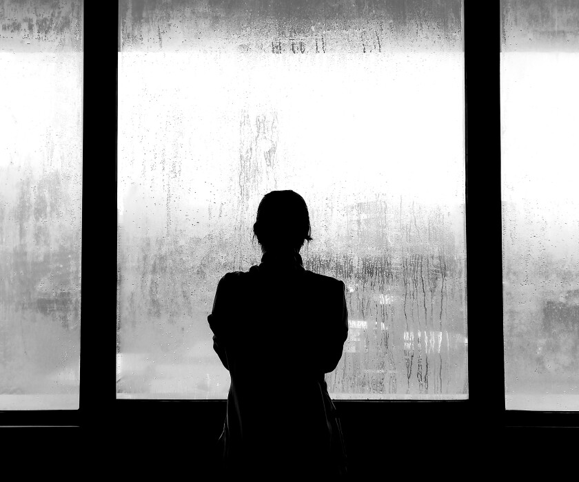 Silhouette of woman outside through a fogged over window. The photo is black-and-white.