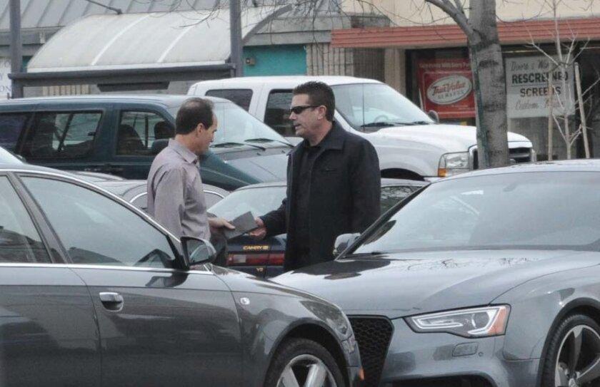 An FBI photo shows former KPMG partner Scott London, left, allegedly accepting cash from jeweler Bryan Shaw.