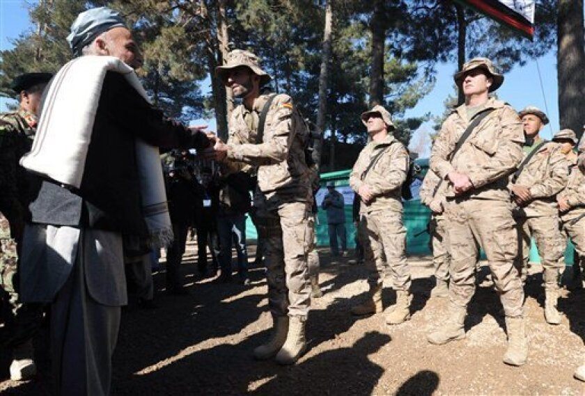 Ashraf Ghani Ahmadzai, left, head of the Transition Commission shakes hand with a Spanish soldier part of the NATO- led Internationals Security Assistance Force (ISAF) during the second phase of transfer of authority ceremony from the NATO- led troops to Afghan security forces in Qalay-e-Naw, Badghis province, west of Kabul, Afghanistan, Tuesday, Jan. 31, 2012.The security responsibilities of two districts including the provincial capital of Badghis province was handed over from the NATO- led forces to Afghan security forces. The process of taking over security from over 130,000-strong NATO-led ISAF forces by Afghan troops would be completed by the end of 2014 when Afghanistan will take over the full leadership of its own security duties from U.S. and NATO forces. (AP Photo/Shamil Azad)