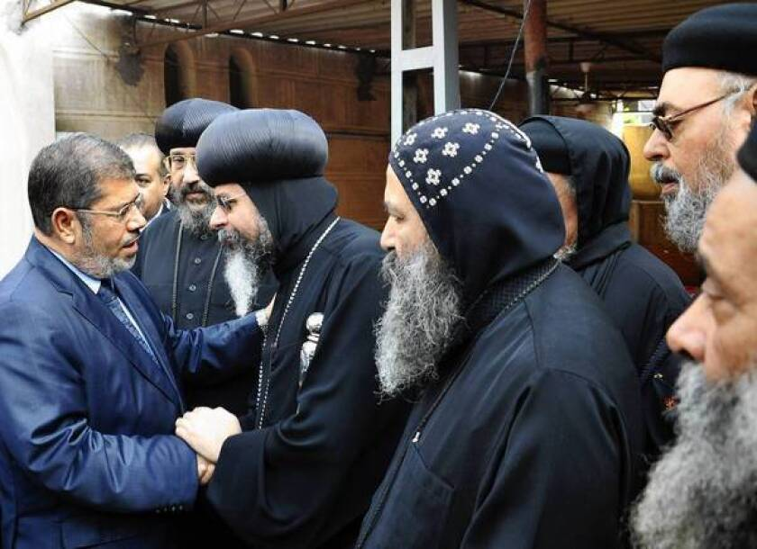 Egypt's Islamist president, Mohamed Morsi, left, receives condolences from Coptic Christian priests at his sister's funeral in Sharqiya. Fighting between Israel and Hamas has put Morsi's government in the spotlight.