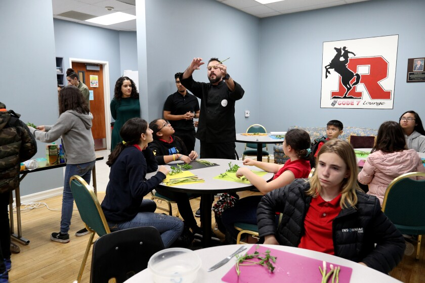 Chef Santiago Segura shows cooking students where to cut the vegetables at the Roosevelt Middle School enrichment culinary class on Thursday. The students made fettuccine Alfredo.
