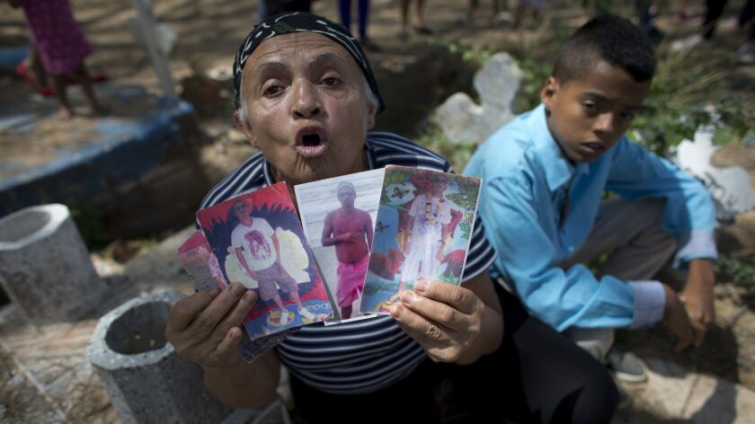 Yajaira Rojas shows photos of her late son Alix Eduardo Diaz, during his funeral at the Municipal Ce