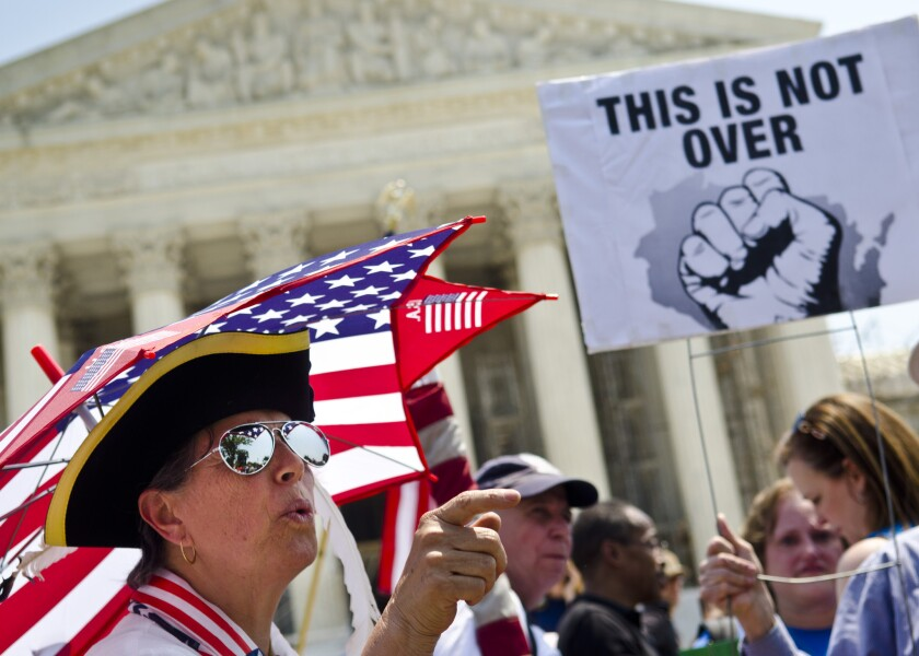An argument ensues between Affordable Care Act demonstrators outside the Supreme Court in Washington.