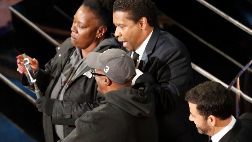 Denzel Washington, center, mock-marries an engaged couple with Jimmy Kimmel looking on during the 89th Academy Awards.