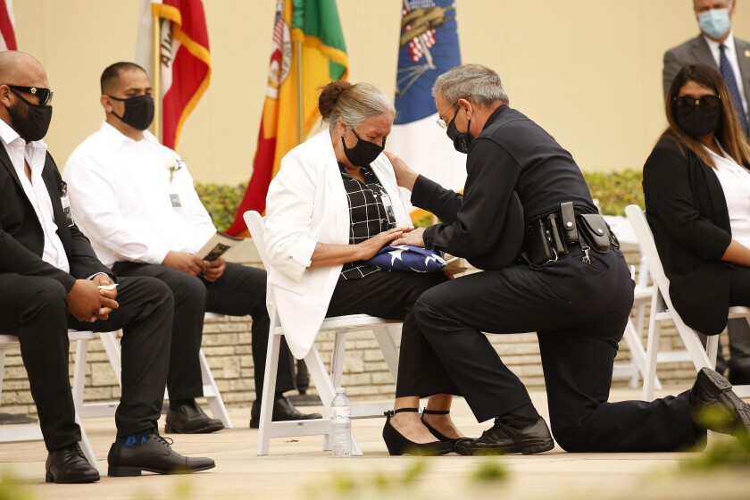 LAPD Chief Michel Moore presents the U.S. flag to Maria Martinez while others sit near her