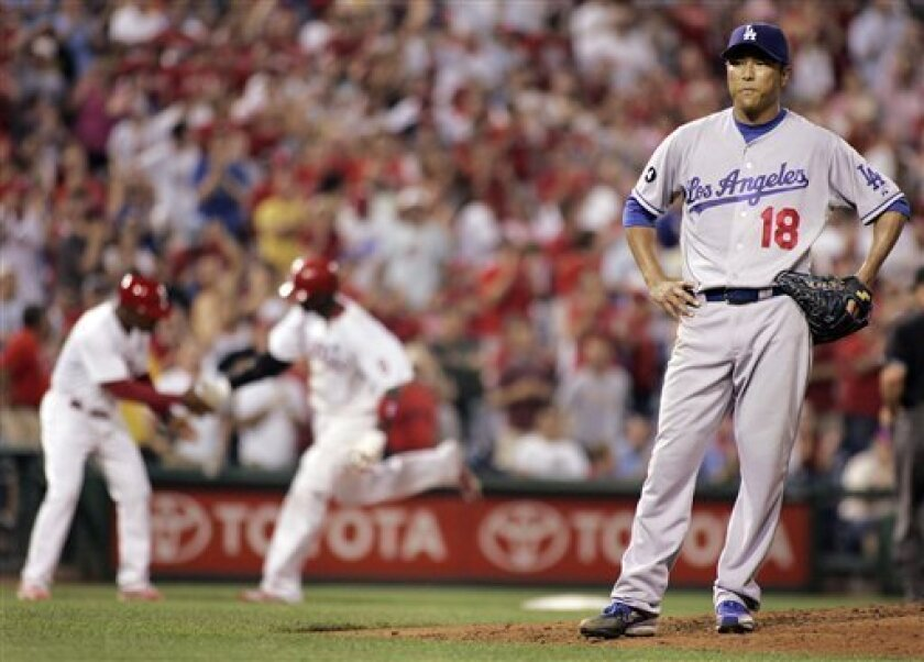 Los Angeles Dodgers starting pitcher Hiroki Kuroda, right, waits on the mound while Philadelphia Phillies' Ryan Howard, center, rounds third after hitting a home run during the sixth inning of a baseball game on Wednesday, June 8 2011, in Philadelphia. The Phillies won 2-0. (AP Photo/Tom Mihalek)