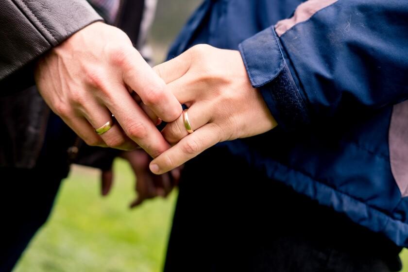 A close-up of a man and woman's entwined hands; each wears a gold wedding band.