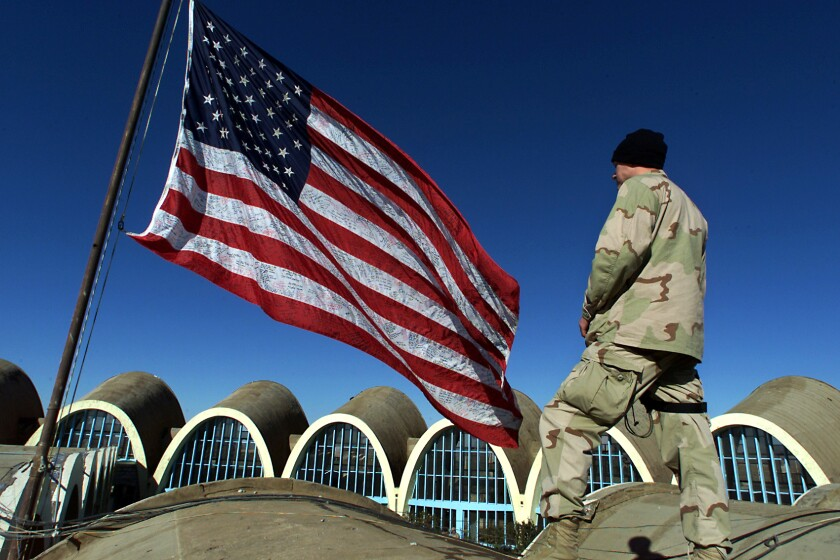 A man in camouflage stands alongside a U.S. flag.