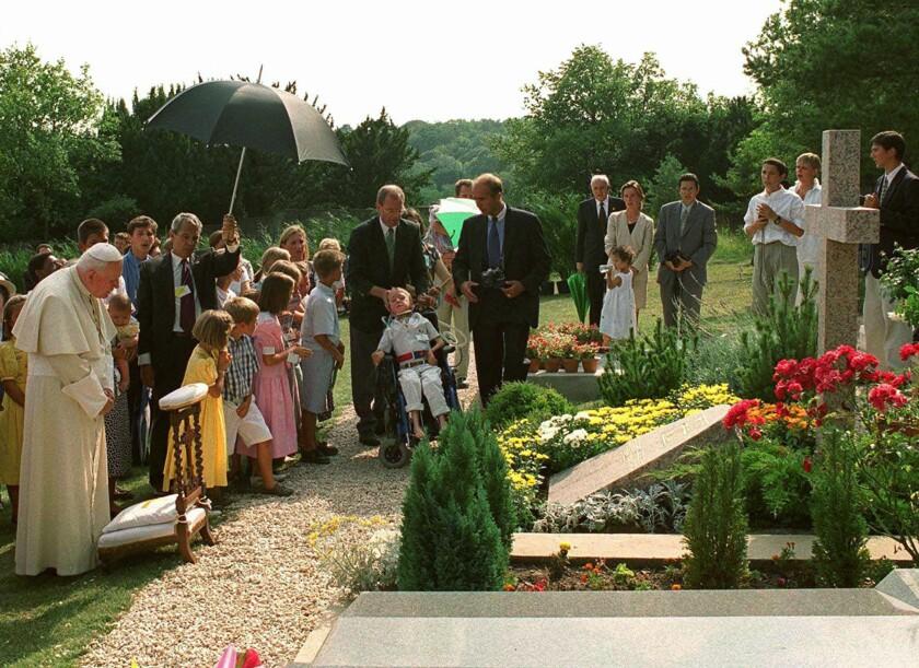 Pope John Paul II by the grave of  geneticist Jerome Lejeune near Paris.