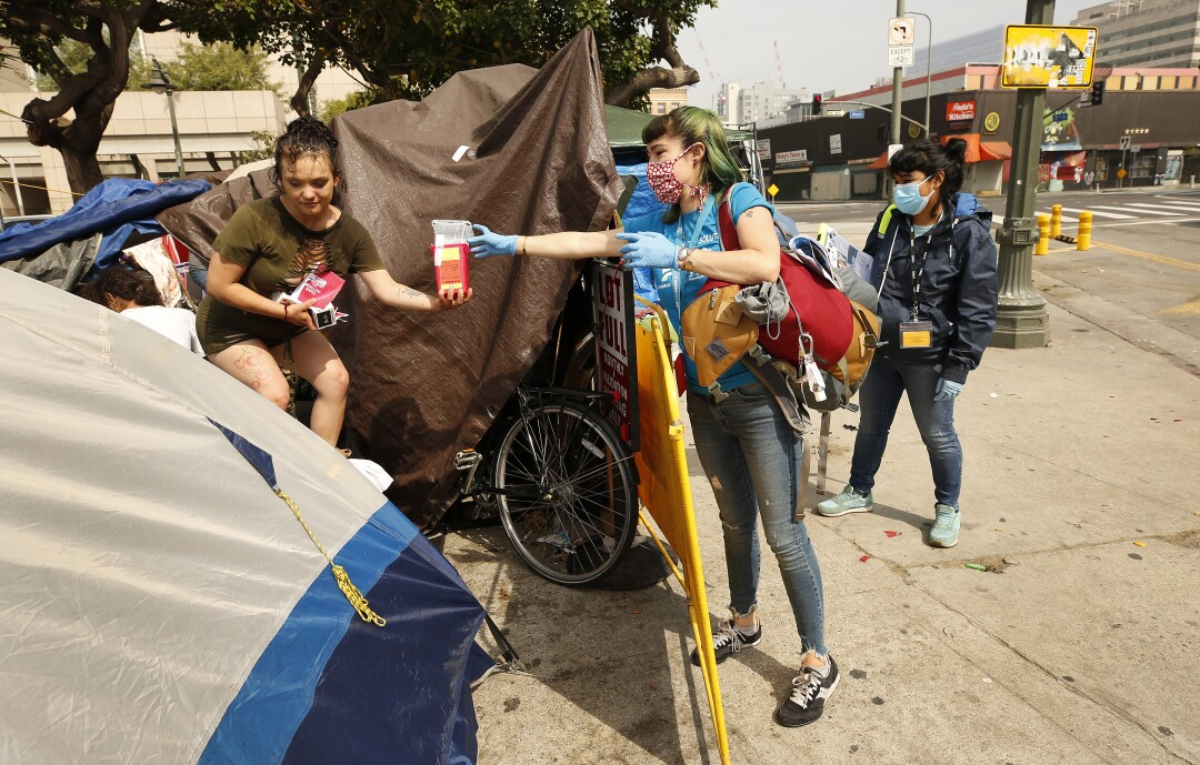 Outreach worker Ciara DeVozza, right, talks with 20-year-old homeless woman on the streets of skid row in Los Angeles