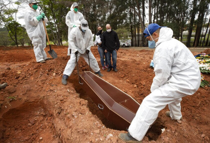 Darick Caverni and his wife Michelle watch as cemetery workers in protective clothing lower the coffin that contain the remains of his 88-year-old aunt Wilma Caverni, who died of the new coronavirus, at the Vila Formosa cemetery in Sao Paulo, Brazil, Wednesday, July 15, 2020. Brazil is nearing 2 million cases of COVID-19 and 75,000 deaths. (AP Photo/Andre Penner)