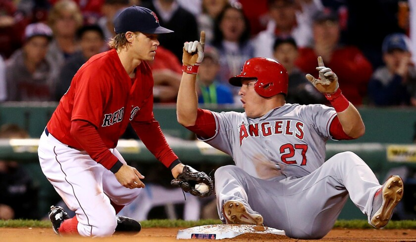 Angels' Mike Trout slides safely into third past Boston Red Sox's Brock Holt during an Angels 12-5 rout over the Red Sox on Friday.