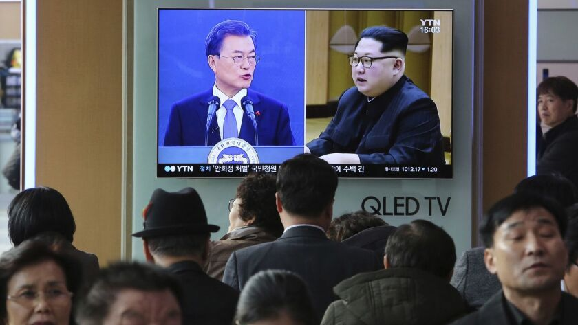 A TV screen on March 7 at a Seoul railway station shows images of South Korean President Moon Jae-in, left, and North Korean leader Kim Jong Un.