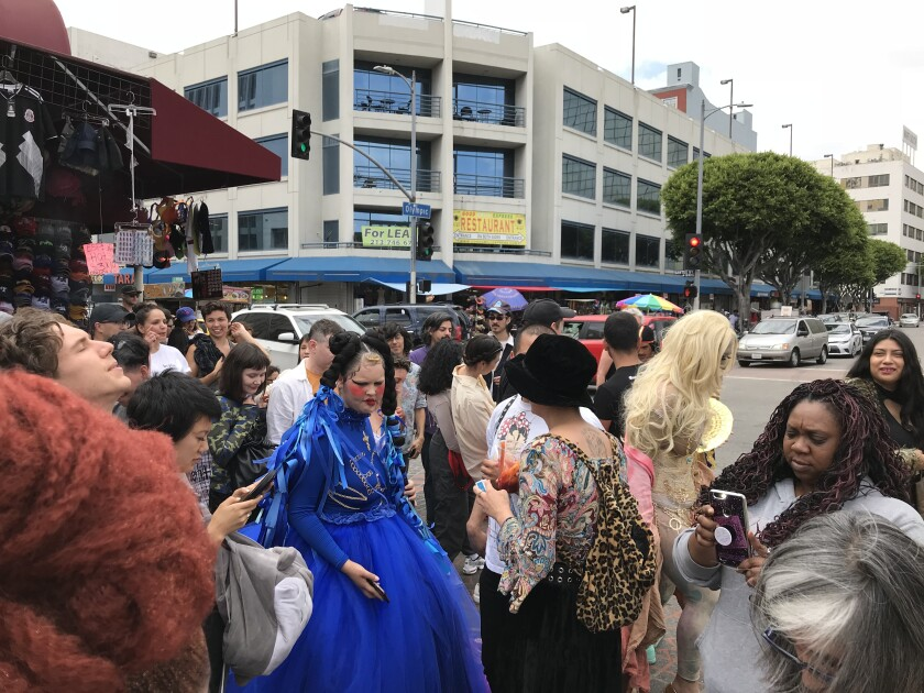 Moe Guinevere, dressed in a blue gown designed by Gabriela Ruiz, a.k.a. Leather Papi, crosses a street near Santee Alley.