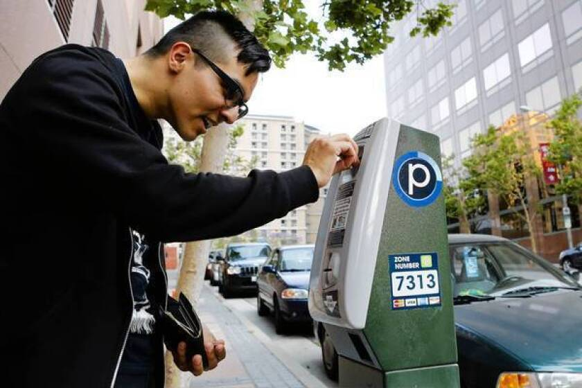 Ross Cuevas of Westwood puts coins in a parking meter at 3rd Street and Grand Avenue in downtown Los Angeles.