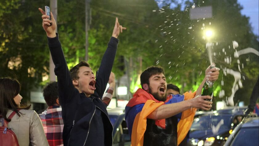 A man with a national flag around his shoulders brandishes a bottle of sparkling wine in Yerevan to celebrate the resignation of Armenian Prime Minister Serzh Sargsyan on April 23, 2018.
