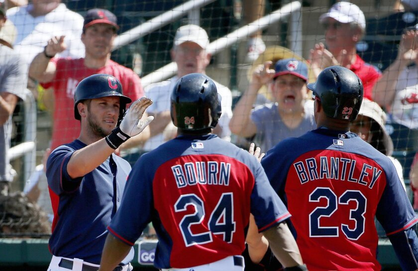 Cleveland Indians' Yan Gomes, left, gives high-fives to Michael Bourn (24) and Michael Brantley (23) after both scored on a double by Carlos Santana during the second inning of a spring training baseball game against the Seattle Mariners Tuesday, March 31, 2015, in Goodyear, Ariz. (AP Photo/Ross D. Franklin)