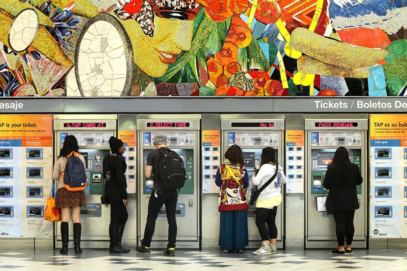 Metro passengers add fares to their ticket cards at the Universal City Red Line station. A proposal that the Metro board will consider Thursday could raise fares as much as 117% over the next eight years.