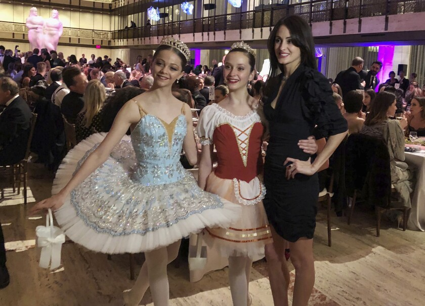 """FILE - In this image taken from video, choreographer Melanie Hamrick poses for a photo with young dancers at the gala of Youth America Grand Prix, the world's largest ballet scholarship competition, on April 18, 2019, after the U.S. premiere of her new ballet, """"Porte Rouge"""" (Red Door). Hamrick's Live Arts Global company is producing """"A Night at the Ballet,"""" a free streaming event that premieres this week. The event will treat ballet-starved fans to dancers from America's top companies performing excerpts of classical ballets like """"Romeo and Juliet, """"The Nutcracker"""" and """"Don Quixote."""" (AP Photo/Aron Ranen, File)"""