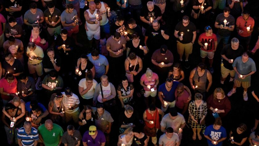 Mourners on June 13, 2016, observe a moment of silence for the Pulse nightclub shooting victims during a vigil outside the Dr. Phillips Center for the Performing Arts in Orlando, Fla.