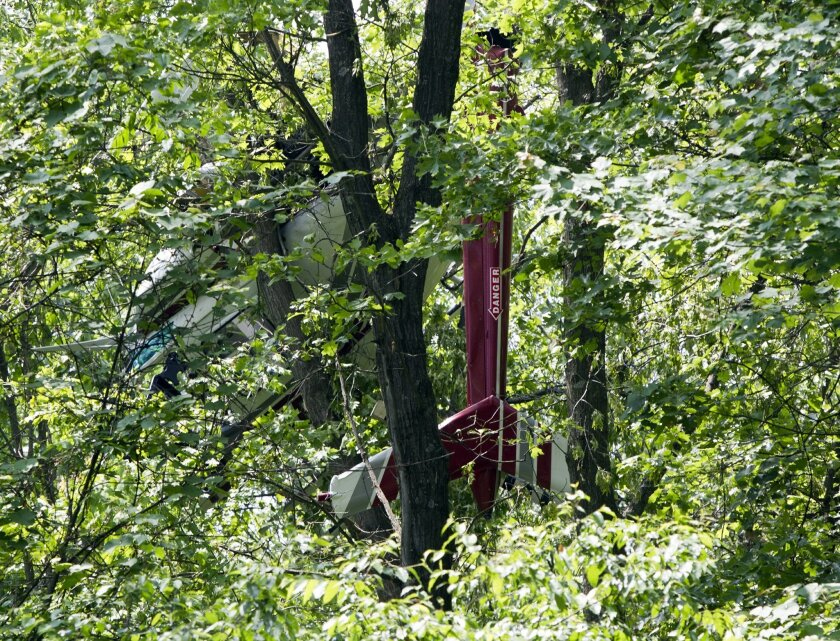 A small helicopter has crashed into a tree in in Caledonia, in western Michigan and is stuck in its branches Friday, May 29, 2015. No injuries have been reported. (Cory Morse/The Grand Rapids Press via AP)