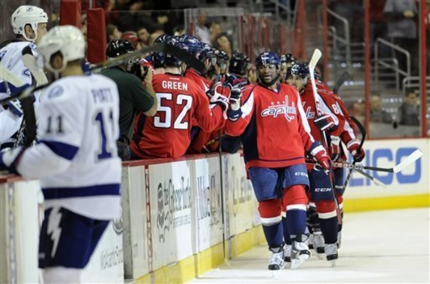Washington Capitals right wing Joel Ward, right, celebrates his goal with teammate Mike Green (52) and others during the second period of an NHL hockey game against the Tampa Bay Lightning, Sunday, April 7, 2013, in Washington. (AP Photo/Nick Wass)