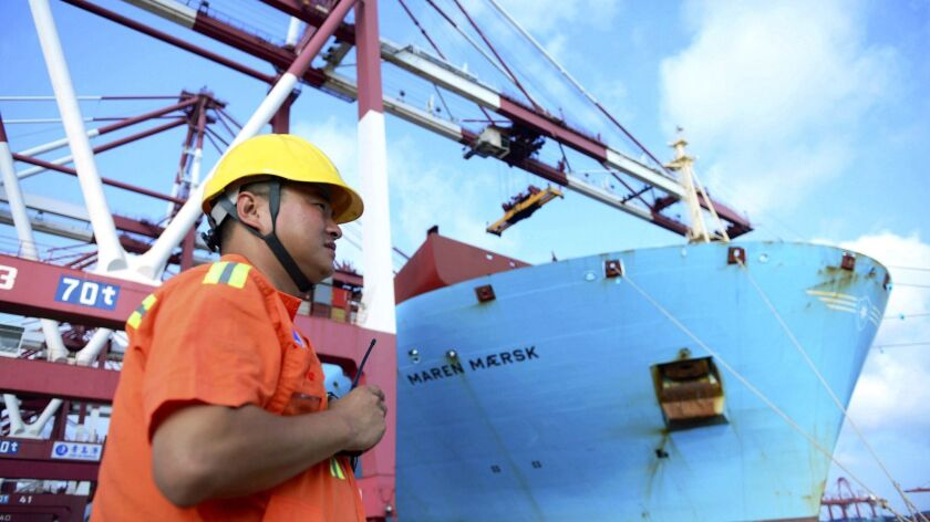 A worker stands near a container ship Aug. 8 at a port in Qingdao in eastern China's Shandong province.
