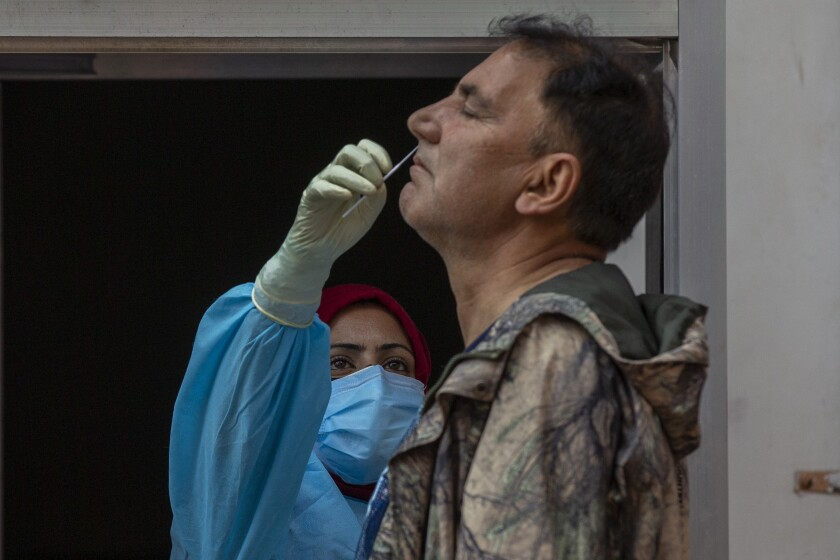 FILE- In this May 11, 2021 file photo, a health worker takes a nasal swab sample of a Kashmiri man to test for COVID-19 in Srinagar, Indian controlled Kashmir. A dip in the number of coronavirus cases in Mumbai is offering a glimmer of hope for India, which is suffering through a surge of infections. (AP Photo/ Dar Yasin, File)