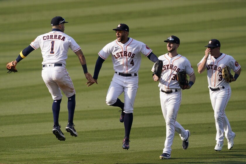 Houston Astros' Carlos Correa, from left, celebrates with George Springer, Kyle Tucker and Myles Straw.