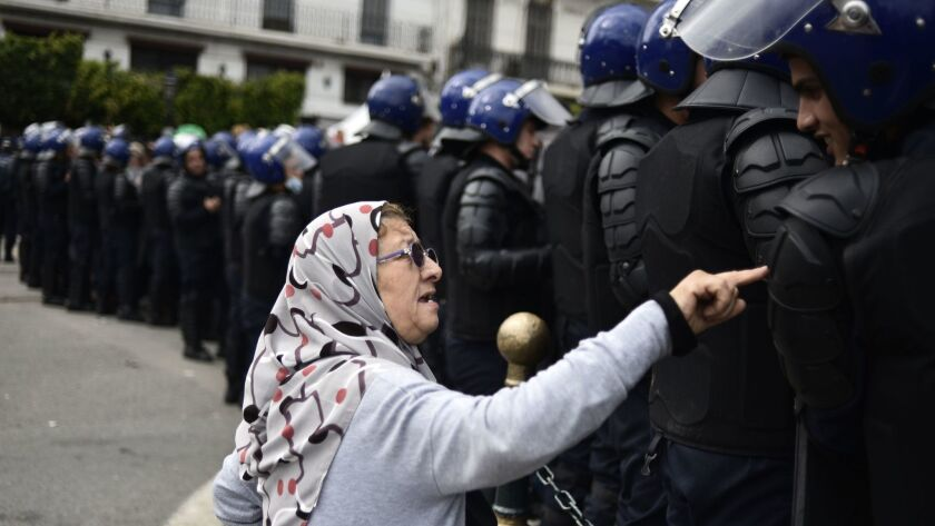 An Algerian woman talks to a member of the security forces blocking access to a protest area in Algiers, the capital on April 10.