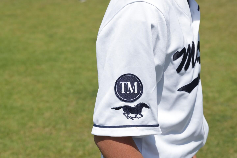 The game day uniform for SDA baseball includes a memorial patch to honor Tom Martinez.