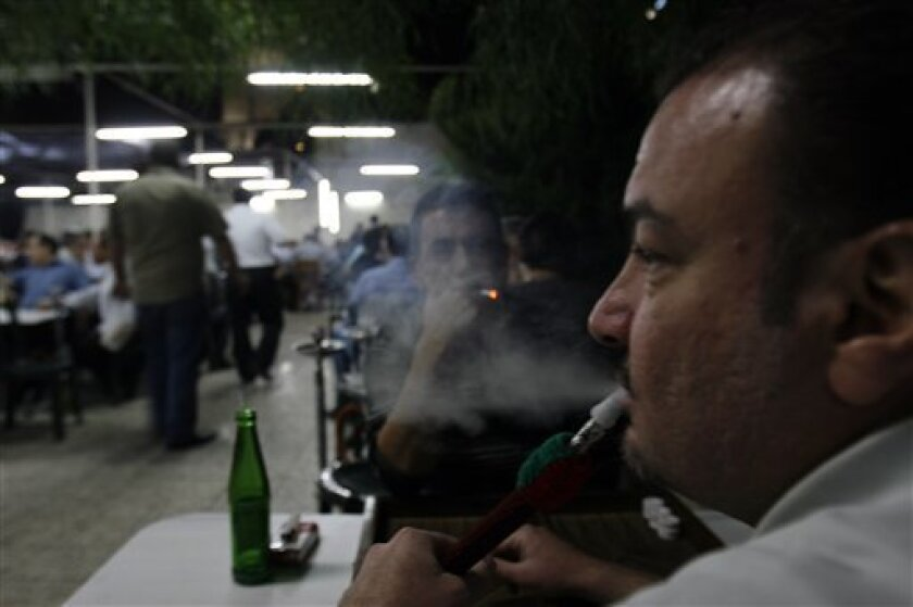 Syrians smoke water pipes at a caf�n downtown Damascus, Syria on Monday, October 12, 2009. Syrian President Bashar Assad issued late Sunday a decree banning smoking and selling and providing tobacco products at certain public utilities. The decree also prevents smoking during meetings, conferences, lectures, training activities and official symposiums. The decree also prevents the promotion and advertising of tobacco products and smoking and imposes fines for violating the decree, which will be officially applied after six months. (AP Photo/Bassem Tellawi)