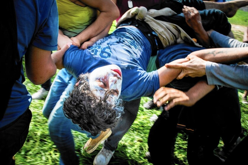 A boy, knocked unconscious by a rubber bullet, is carried out of the action at Idomeni.