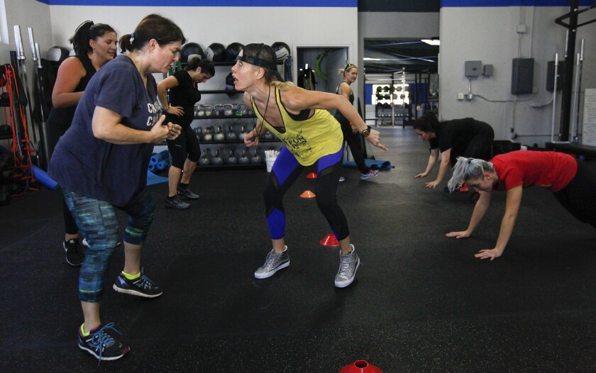 Fitness trainer Lacey Stone, center, motivates student Carrie Carr, left, a