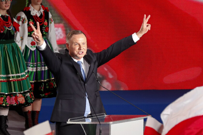 Polish President Andrzej Duda flashes victory signs during a stop in Lowicz on Sunday.