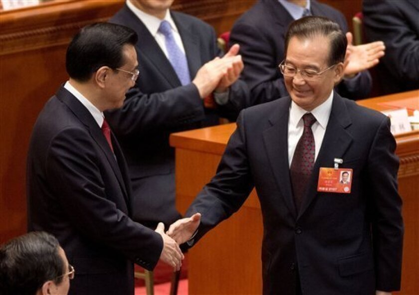 Newly-named Chinese Premier Li Keqiang, left, is greeted by his predecessor Wen Jiabao after delegates voted Li as the new premier during a plenary session of the National People's Congress at the Great Hall of the People in Beijing Friday, March 15, 2013. China named the Communist Party's No. 2 le