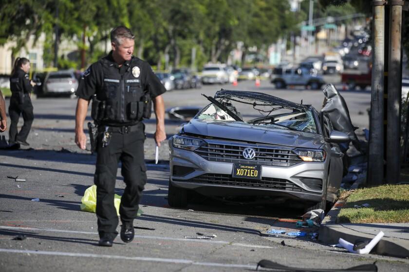 A police officer walks near a smashed car on a city street.