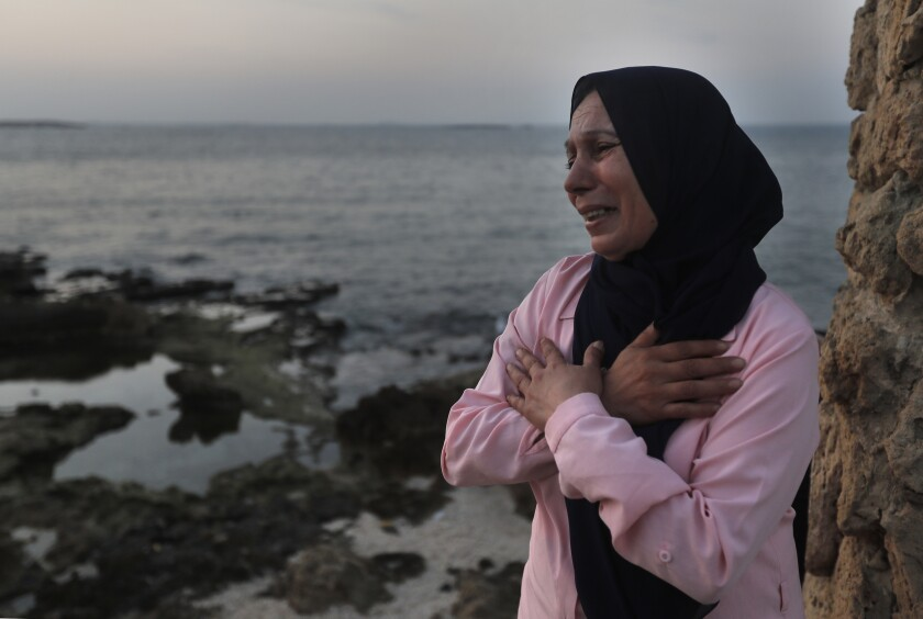A woman cries and prays her son's safe return.