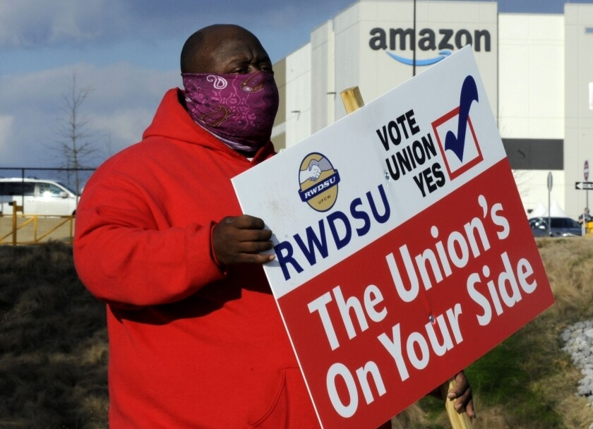 A man holds a pro-union sign outside an Amazon facility in Bessemer, Ala.