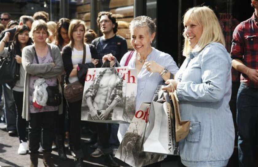 In this photo of Oct. 25, 2010, women show off their shopping bags from Abercrombie & Fitch as they leave the Fifth Ave. store in New York. Retailers are reporting solid revenue gains for October. But it took heavy discounting on coats and other cold-weather items to get shoppers to spend amid unusually warm temperatures. (AP Photo/Mark Lennihan)